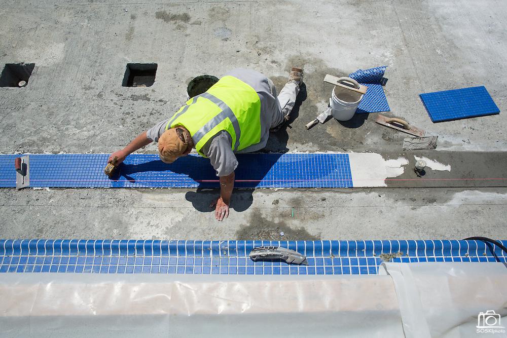 Richard Lamb lays down lane marker tiles in the warming pool at Milpitas High School in Milpitas, California, on July 18, 2014. (Stan Olszewski/SOSKIphoto)