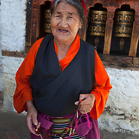 Asia, Bhutan, Thimpu. Bhutanese Woman and Prayer Wheels.