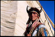 Plains Indian reenactor Michael Terry, a Florida Seminole, poses by buffalo-hide teepee he made; Ft Union Natl Historic Site, ND