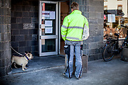 "A man and dogs are practicing ""social distancing"" in front of a backery shop in Oberursel-Stierstadt."