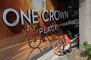 A rental Mobike leans against a tree next to an illustration of a cycling utopia at a new development called One Crown Place on Sun Street near Liverpool Street Station in the City of London, the capitals financial district - aka the Square Mile, on 8th August, in London, England.