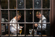 Two businessmen look at their phones in the window of a pub in Lime Street in the heart of the capital's financial district, on 26th June, in the City of London, England.