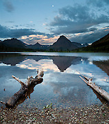 """Dawn light illuminates Pray Lake and Sinopah Mountain (8271 feet or 2521 meters) in Glacier National Park, Montana, USA. Since 1932, Canada and USA have shared Waterton-Glacier International Peace Park, which UNESCO declared a World Heritage Site (1995) containing two Biosphere Reserves (1976). Rocks in the park are primarily sedimentary layers deposited in shallow seas over 1.6 billion to 800 million years ago. During the tectonic formation of the Rocky Mountains 170 million years ago, the Lewis Overthrust displaced these old rocks over newer Cretaceous age rocks. Glaciers carved spectacular U-shaped valleys and pyramidal peaks as recently as the Last Glacial Maximum (the last """"Ice Age"""" 25,000 to 13,000 years ago). Of the 150 glaciers existing in the mid 1800s, only 25 active glaciers remain in the park as of 2010, and all may disappear by 2020, say climate scientists. (Panorama stitched from 3 images.)"""