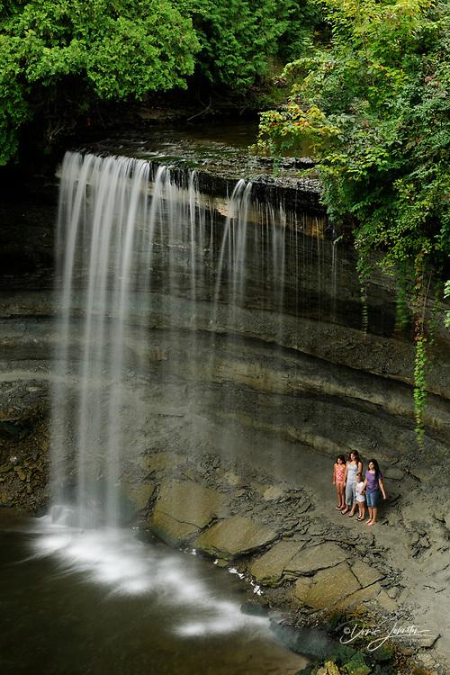 Visitors standing under Bridal Veil Falls, Manitoulin Island- Kagawong, Ontario, Canada