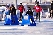 03 JANUARY 2021 - DES MOINES, IOWA: Children use skating trainers at Brenton Skating Plaza in downtown Des Moines. The ice skating rink usually opens in late November and stays open through late February or March, depending on weather. Covid restrictions limited capacity to less than half, skaters were encouraged to social distance, and skaters were required to wear proper face masks. This year the rink was forced to close January 3, after only six weeks, because it wasn't possible to comply with COVID-19 restrictions and still be profitable. Restrictions caused by the Coronavirus pandemic have limited many public events this winter in Iowa.   PHOTO BY JACK KURTZ