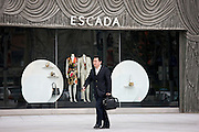 Man with case outside Escada shop on Nanjing Road, central Shanghai, China