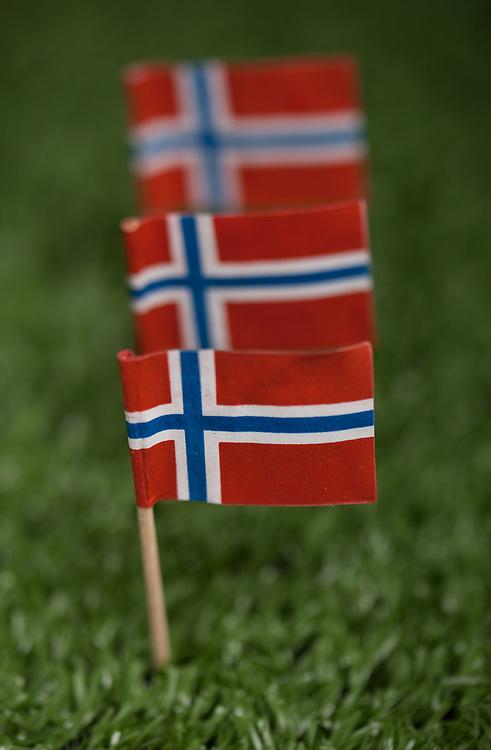 Tre norske flagg på rekke, med trepinne på grønt kunstress. Foto tatt med macro-objektiv, stor dybdeuskarphet.