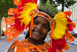 London, August 30th 2015. A girl walks down Ladbroke Grove on her way to join her troupe as revellers await the start of the Notting Hill Carnival family day.