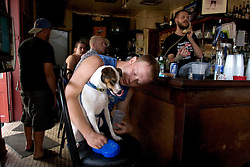 """03 Sept  2005. New Orleans, Louisiana. Post hurricane Katrina.<br /> Johnny White's Sports Bar on Bourbon Street in the French Quarter - with it's claim to """"Never Close."""" The bar has remained open throughout.  John Webster gives his dog Muffin a drink at the bar.<br /> Photo Credit ©: Charlie Varley/varleypix.com"""