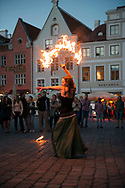 Tallinn, Estonia - July 27, 2015: A young woman from St. Petersburg, Russia, dances with fire for tips in the main square in the Old Town of Tallinn, Estonia.