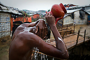 A young man washes himself during a break from heavy rain at the end of the day in Charkmakul, one of the camps sheltering over 800,000 Rohingya refugees, Cox's Bazar, Bangladesh, June 13, 2018. Already, in the first few days of rain, 900 shelters and 200 latrines have been destroyed.