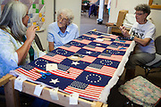 At the Mountainair Senior Center, friends chat while working on a quilt.