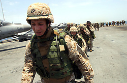 Less than a day before entering Kuwaiti waters, the 11th's commanding officer, Colonel Anthony Haslam, leads the Marines of his command staff on a final conditioning hike around the Belleau-Wood's flight deck in the noon day heat. During the course of the month-long transit to Kuwait, Colonel Haslam has constantly stressed the importance of  conditioning his Marines as much as possible for the temperatures in excess of 120 degrees that they will encounter in Iraq.