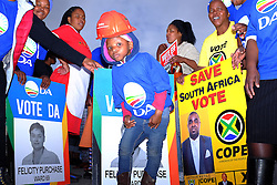 A young boy poses in front of electoral posters for the Democratic Alliance and COPE whilst wearing a red hard hat in support of the Economic Freedom Fighters  in Masiphumelele near Fish Hoek, Cape Town during the 2016 local government elections held across South Africa on the 3rd August 2016<br /> <br /> Photo by - Ron Gaunt / RealTime Images