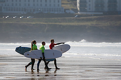 Three surfers carry their surfboards on Fistral Beach in Newquay, Cornwall.