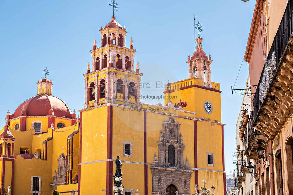 Facade of the Baroque style, Parroquia de Basílica Colegiata de Nuestra Señora de Guanajuato or Guanajuato Basilica in the historic center of Guanajuato City, Guanajuato, Mexico. The massive basilica is painted bright yellow, located in along the Plaza of Peace and was built in 1671.