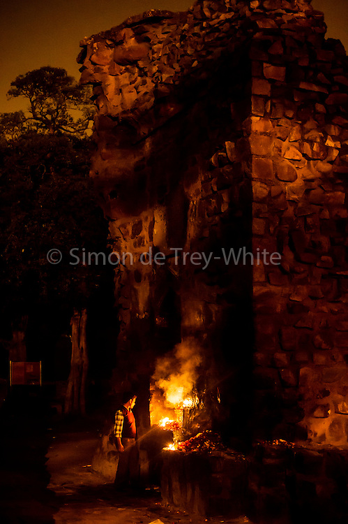 "18th December 2014, New Delhi, India. A man stands by as candles burn in a niche amid the ruins of Feroz Shah Kotla left by believers who prayed and made offerings and asked for wishes to be granted by Djinns in the ruins of Feroz Shah Kotla in New Delhi, India on the 18th December 2014<br /> <br /> PHOTOGRAPH BY AND COPYRIGHT OF SIMON DE TREY-WHITE a photographer in delhi<br /> + 91 98103 99809. Email: simon@simondetreywhite.com<br /> <br /> People have been coming to Firoz Shah Kotla to leave written notes and offerings for Djinns in the hopes of getting wishes granted since the late 1970's. Jinn, jann or djinn are supernatural creatures in Islamic mythology as well as pre-Islamic Arabian mythology. They are mentioned frequently in the Quran  and other Islamic texts and inhabit an unseen world called Djinnestan. In Islamic theology jinn are said to be creatures with free will, made from smokeless fire by Allah as humans were made of clay, among other things. According to the Quran, jinn have free will, and Iblis abused this freedom in front of Allah by refusing to bow to Adam when Allah ordered angels and jinn to do so. For disobeying Allah, Iblis was expelled from Paradise and called ""Shaytan"" (Satan).They are usually invisible to humans, but humans do appear clearly to jinn, as they can possess them. Like humans, jinn will also be judged on the Day of Judgment and will be sent to Paradise or Hell according to their deeds. Feroz Shah Tughlaq (r. 1351–88), the Sultan of Delhi, established the fortified city of Ferozabad in 1354, as the new capital of the Delhi Sultanate, and included in it the site of the present Feroz Shah Kotla. Kotla literally means fortress or citadel."