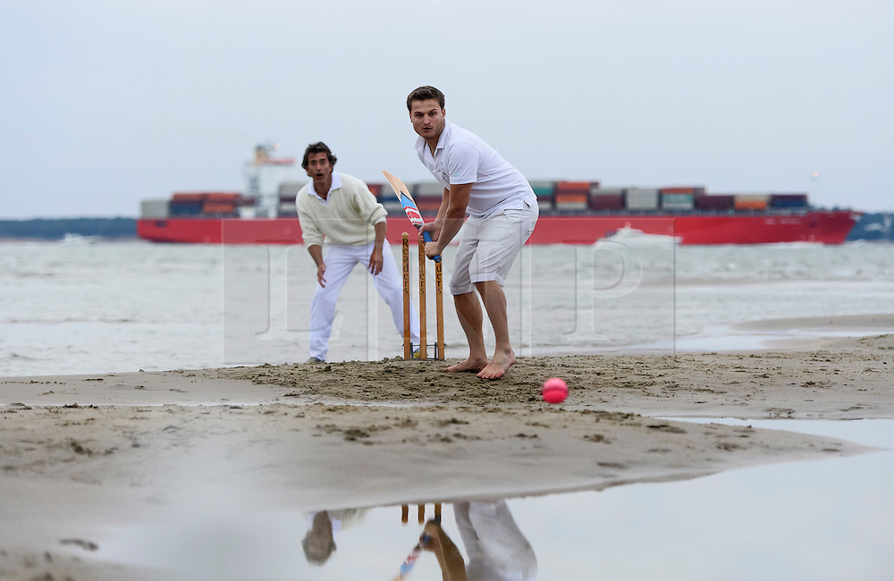© Licensed to London News Pictures. 18/09/2016. Portsmouth, UK. A cargo ship passes by in the background. Teams take part in the  Bramble Bank Cricket Match in the middle of The Solent strait on September 18, 2016. The annual cricket match between the Royal Southern Yacht Club and The Island Sailing Club, takes place on a sandbank which appears for 30 minutes at lowest tide. The game lasts until the tide returns. Photo credit: Ben Cawthra/LNP