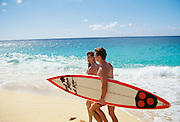 Couple walking on beach with surfboard, Hawaii