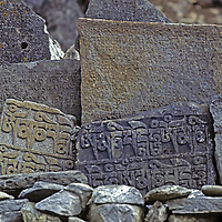 HIMALAYA, NEPAL. Tibetan Buddhist mani stones, carved with prayers and placed in a wall beside Mount Everest Base Camp trail, Khumbu region