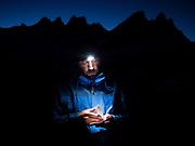 Nathan Rice reads by headlamp below the Southern Pickets at Terror Basin Camp, North Cascades National Park, Washington.