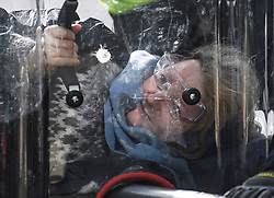 © Licensed to London News Pictures. 10/10/2019. London, UK. An Extinction Rebellion activists holds on to a shield protecting her face as police attempt to cut her free form the road near Trafalgar Square in Westminster, central London where campaigners have been demonstrating for a fourth day running. The climate change group have blockaded the Westminster area, demanding that the government takes immediate and decisive action on climate change. Photo credit: Ben Cawthra/LNP