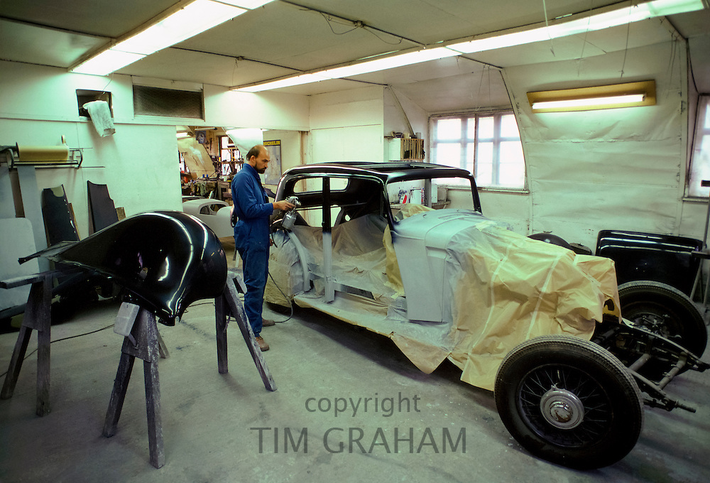Engineer working on spray painting bodywork of vintage car being restored at Ashton Keynes Vintage Restorations in Wiltshire, UK