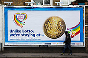A young man wearing a hoodie jumper walks past a large bill board poster for the Health Lottery in Dalston, Hackney, London.  The Health Lottery is a national lottery game which is specifically designed to raise money for local health causes and is separate to the main United Kingdom national lottery, Lotto.