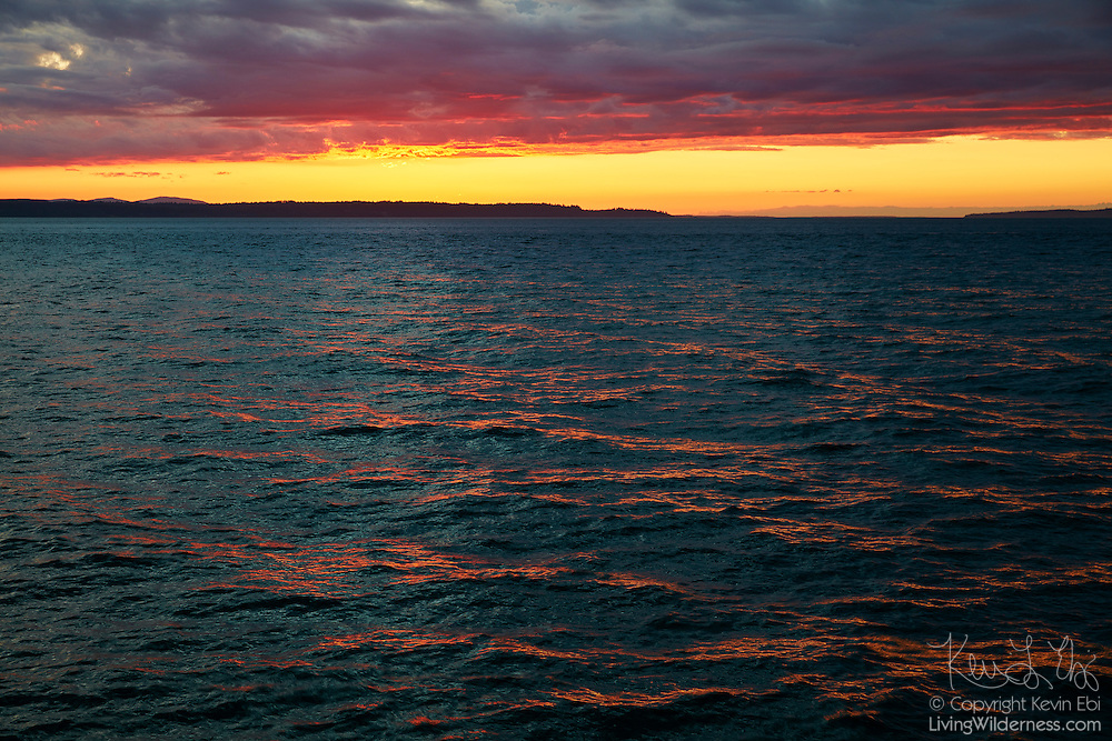 The red color from a fiery sunset is reflected on the ripples of Puget Sound in this view from Edmonds, Washington.