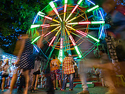 24 NOVEMBER 2015 - BANGKOK, THAILAND: A Ferris Wheel at the Wat Saket temple fair. Wat Saket is on a man-made hill in the historic section of Bangkok. The temple has golden spire that is 260 feet high which was the highest point in Bangkok for more than 100 years. The temple construction began in the 1800s in the reign of King Rama III and was completed in the reign of King Rama IV. The annual temple fair is held on the 12th lunar month, for nine days around the November full moon. During the fair a red cloth (reminiscent of a monk's robe) is placed around the Golden Mount while the temple grounds hosts Thai traditional theatre, food stalls and traditional shows.       PHOTO BY JACK KURTZ