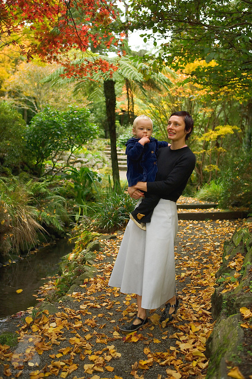 A mother and her young boy in a garden, during autumn.