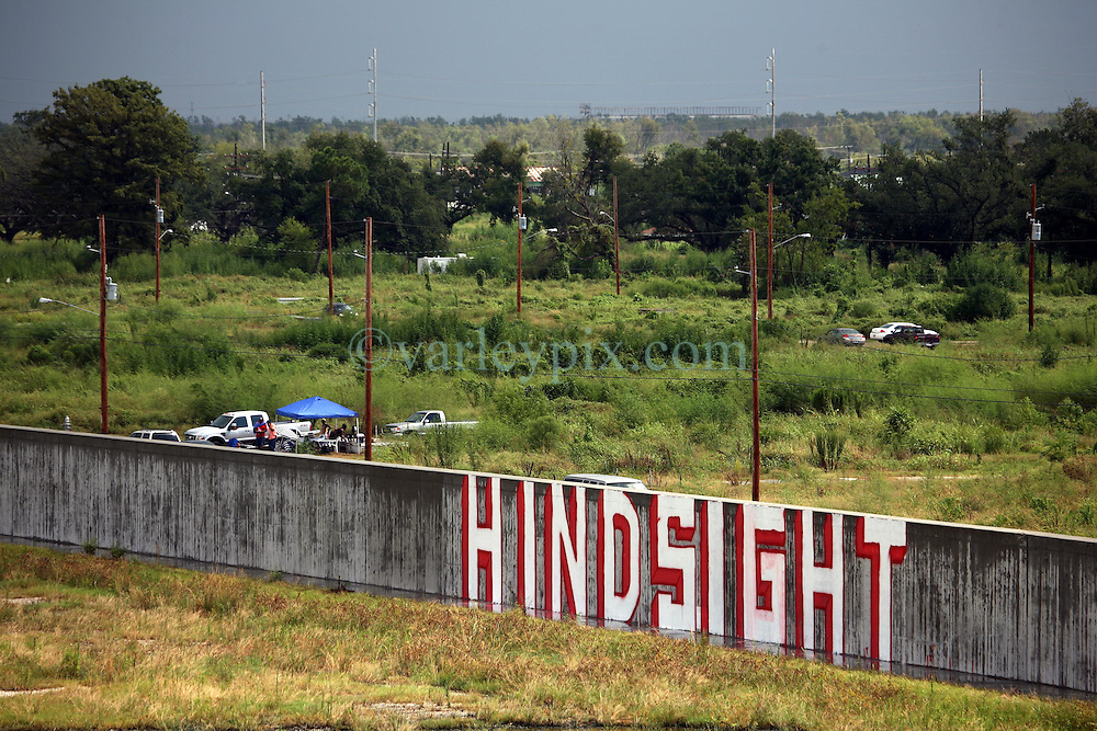 29 August 2007. Lower 9th Ward, New Orleans, Louisiana. <br /> Second anniversary of Hurricane Katrina. Graffiti tags the industrial canal levee at the same spot where the levee breached during hurricane Katrina killing hundreds of New Orleanians. The simple word, 'Hindsight' mirrors the attitude of many residents struggling to return to the still derelict and decimated Lower 9th Ward.<br /> Photo credit©; Charlie Varley/varleypix.com
