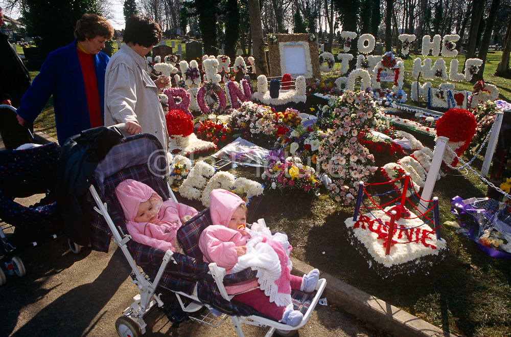 London Eastender babies and mothers pause to admire the community memorial to notorious 60s gangster twin Ronnie Kray during East End funeral at Chingford cemetery in Essex. The floral tributes are in honour of the recently deceased Ronald, commonly referred to as Ron or Ronnie who suffered from paranoid schizophrenia. Ronnie and his twin brother Reggie were involved in armed robberies, arson, protection rackets and violent assaults including torture. During the 1950s and 60s. They terrorised their organised crime competitors but were loved by the communities of East London. The Kray gangster twins were eventually jailed separately in 1969 and Ronnie remained in Broadmoor (psychiatric) Hospital until his death on 17 March 1995.
