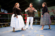 Two 2 female wrestlers with referee at start of match in ring. Lucha Libre wrestling origniated in Mexico, but is popular in other latin Amercian countries, including in La Paz / El Alto, Bolivia. Male and female fighters participate in the theatrical staged fights to an adoring crowd of locals and foreigners alike.