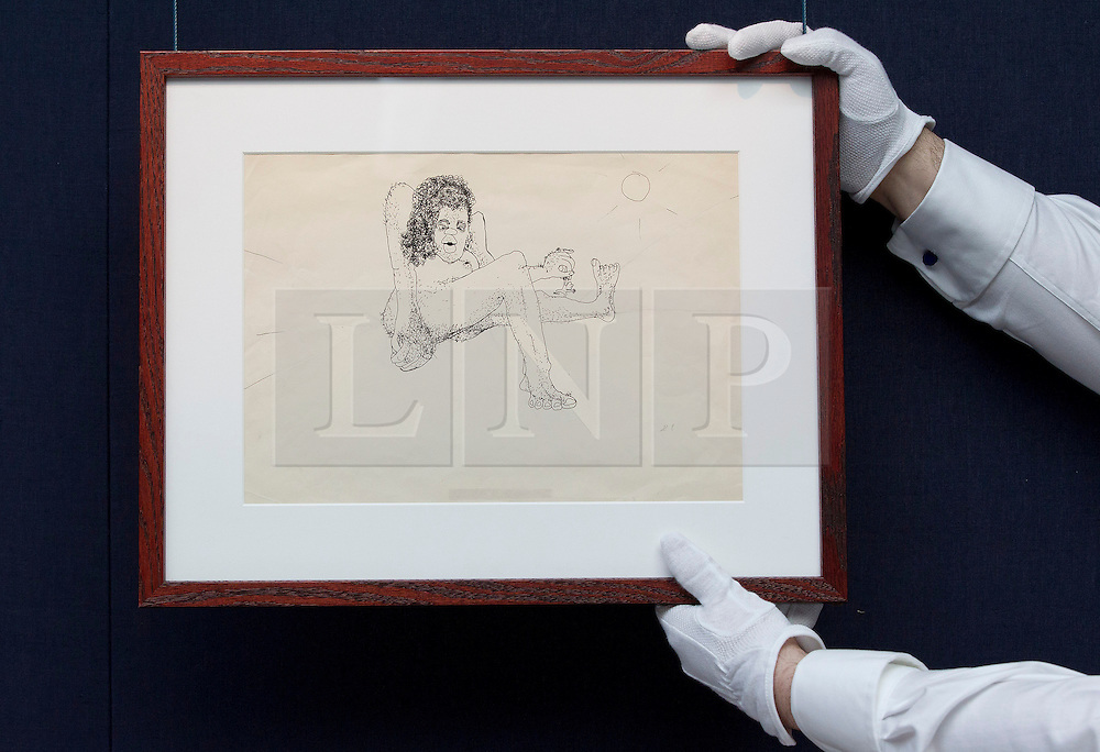 """© Licensed to London News Pictures. 21/03/2014. London, UK. A member of Sotheby's auction house staff adjusts 'untitled illustration of a hairy woman holding a miniature man by the arm' (GB£12,000-15,000) by the late Beetles singer John Lennon, allegedly the piece that brought him to the attention of his future wife Yoko Ono, during the press view for a new sale at Sotheby's auction house in London today (21/03/2014). The auction, entitled """"You Might Well Arsk"""", features original drawings and manuscripts by the singer from 1964-1965. Photo credit: Matt Cetti-Roberts/LNP"""
