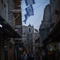 In the Old City of Jerusalem, Israeli flags fly from buildings acquired by Jewish Settlers in the Arab quarter