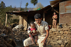 Holding his youngest child, Durga, now 26, sits in frustration in front of the rebuilt shed he shares with Niruta, now 24, their three children, a water buffalo, and a handful of chickens and goats. <br /> <br /> Niruta and Durga were married 9 years ago, when they were just 14 and 16 years old in the Kagati village of Nepal. The 2015 earthquakes devastated Nepal and left girls and women in an increasingly vulnerable position, leading experts to believe child marriage rates will increase over the coming years.