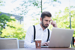 Businessman working on laptop in outdoor cafe, Munich, Bavaria, Germany