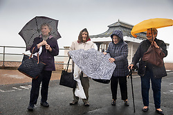 © Licensed to London News Pictures. 14/08/2019. West Sussex, UK. A group of day-trippers from Bermondsey, south London struggle with an umbrella (C) as they brave the wind and rain on the seafront at Worthing on the south coast. Parts of the United Kingdom are exeriencing heavy unseasonable rain today. Photo credit: Peter Macdiarmid/LNP