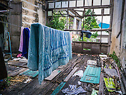 20 APRIL 2013 - BANGKOK, THAILAND:  Firefighters' laundry dries in the old Customs House in Bangkok. The old Customs House was once the financial gateway to Thailand (before 1932 called Siam). It was designed by an Italian architect in the 1880s. In the 1950s, customs moved to new, more modern building and the Customs House became the headquarters for the Marine firefighters. The firefighters now live in the decrepit buildings with their families.  PHOTO BY JACK KURTZ