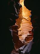 Jammed log looming between gaping walls of a slickrock slot canyon, Colorado Plateau in Northern Arizona.  PW
