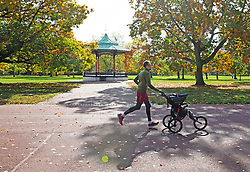 ©Licensed to London News Pictures 14/10/2020  <br /> Greenwich, UK. A dad jogging with a child in a buggy. Autumn sunshine makes a brief appearance today in Greenwich park, Greenwich, London. Photo credit:Grant Falvey/LNP