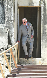 The Prince of Wales steps out of a doorway once used by slaves as they were taken to waiting ships, during a visit to Osu Castle, also known as Fort Christiansborg in Accra, Ghana, on day four of his trip to west Africa with the Duchess of Cornwall.