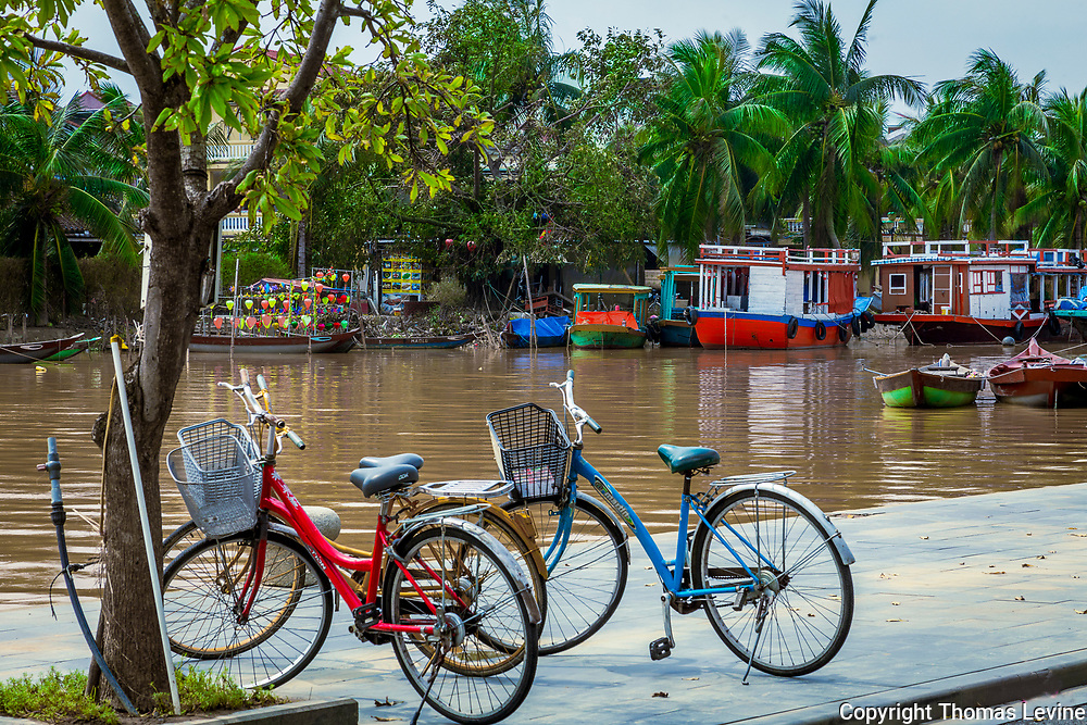 Dec.1, 2020, Hoi An: Thu Bon River in Old Town. Bicycles, boats and palm trees on either side of the river. RAW to Jpg