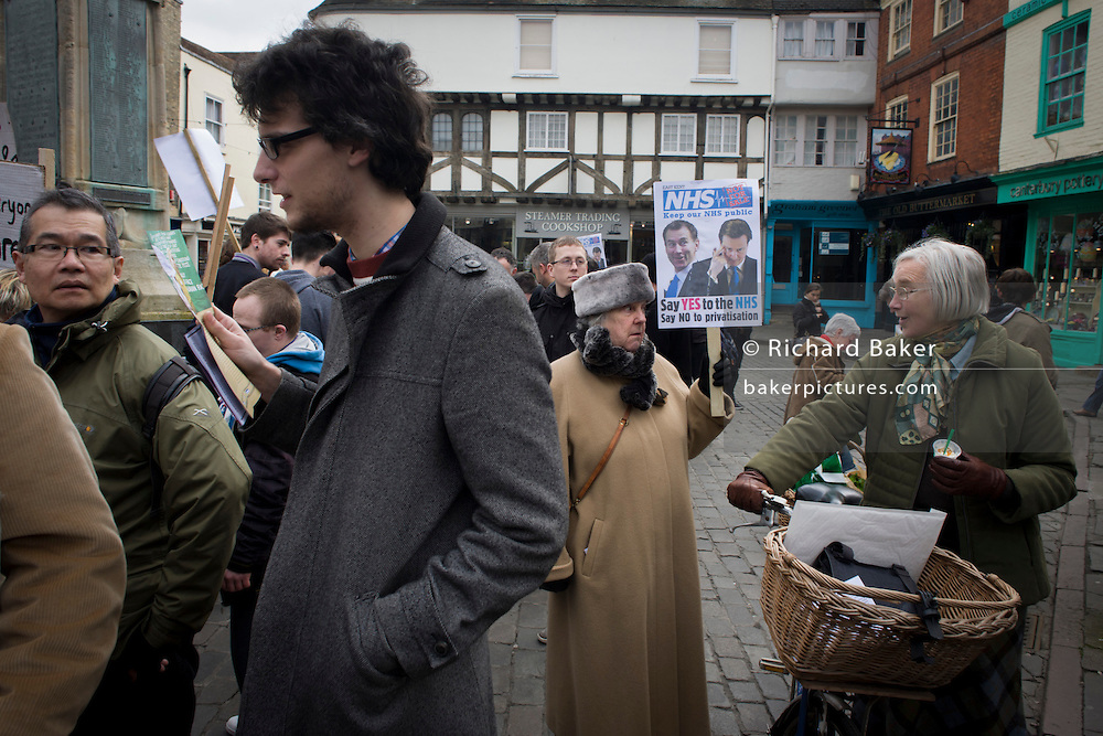 Students and elderly middle-class voters, protests over coalition plans over the NHS, holding a placard in Butter Market in the centre of Canterbury. Health Secretary Jeremy Hunt and David Cameron are parodied on the poster.