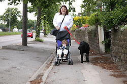 Mother with her baby son in his buggy walking the pet dog,