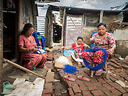 02 AUGUST 2015 - BHAKTAPUR, NEPAL:  Women make tourist curios in front of their temporary shelters in Bhaktapur. The Nepal Earthquake on April 25, 2015, (also known as the Gorkha earthquake) killed more than 9,000 people and injured more than 23,000. It had a magnitude of 7.8. The epicenter was east of the district of Lamjung, and its hypocenter was at a depth of approximately 15 km (9.3 mi). It was the worst natural disaster to strike Nepal since the 1934 Nepal–Bihar earthquake. The earthquake triggered an avalanche on Mount Everest, killing at least 19. The earthquake also set off an avalanche in the Langtang valley, where 250 people were reported missing. Hundreds of thousands of people were made homeless with entire villages flattened across many districts of the country. Centuries-old buildings were destroyed at UNESCO World Heritage sites in the Kathmandu Valley, including some at the Kathmandu Durbar Square, the Patan Durbar Squar, the Bhaktapur Durbar Square, the Changu Narayan Temple and the Swayambhunath Stupa. Geophysicists and other experts had warned for decades that Nepal was vulnerable to a deadly earthquake, particularly because of its geology, urbanization, and architecture.      PHOTO BY JACK KURTZ