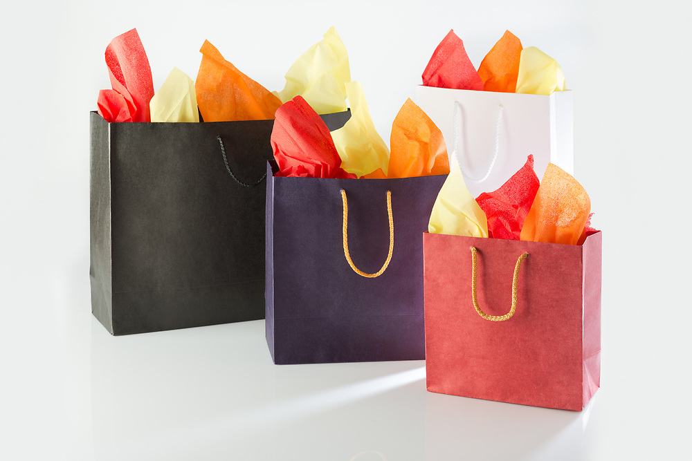 Shopping bags with color papers against a white background