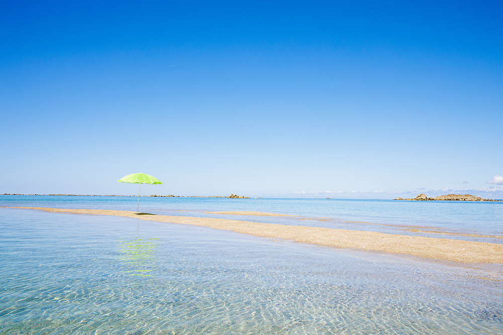 Umbrella reflecting in the crystal clear water surrounding the deserted sandbank at the Minquiers off the coast of Jersey, Channel Islands