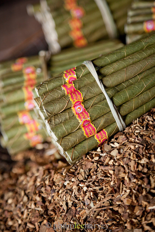 Cheroots, small local cigars, bound and sitting on loose leaf tobacco, are ready for sale. Inle Lake, Shan state, Myanmar